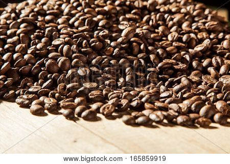 Roasted coffee beans on wood background. Detailed close up