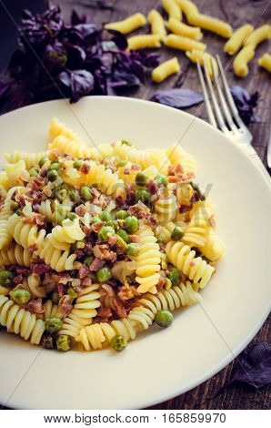 Fusilli with prosciutto and green pease on old wooden background. Traditional Italian pasta with fresh basil. Selective focus.