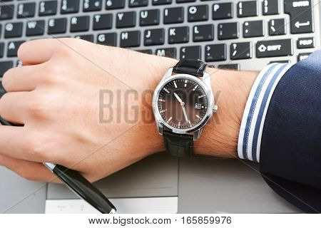 Close-up shot of a watch on a businessman wrist suggesting poor time management or being out of time or running late