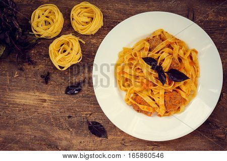 Tagliatelle with meatballs on wooden background. Traditional Italian pasta with a spicy tomato based meat sauce garnished with fresh basil. Top view.