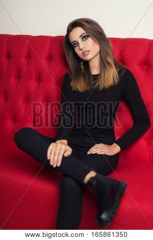 beautiful girl in black sitting on a red couch