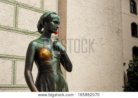 Juliet capulet statue in munich germany july 2015 with shiny breast and deep red flower behind her ear