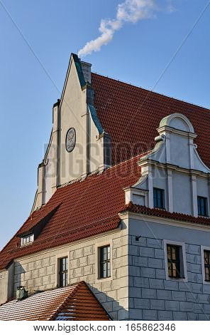 Building with the coat of arms and roof with red tile roofs