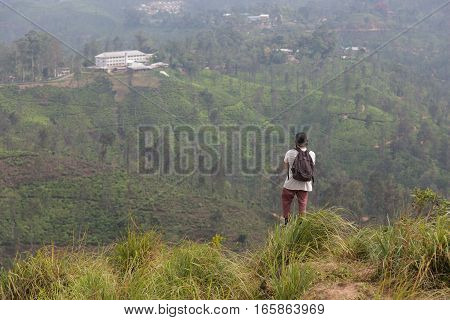 Traveler enjoying pristine nature and beautiful view of tea plantations from the top of Small Adams peak near Ella, Sri Lanka. Tracking outdoors tourist adventure.