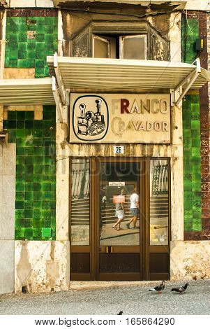 Door to closed stamp shop in Lisbon, Portugal july 2015 - green tiles
