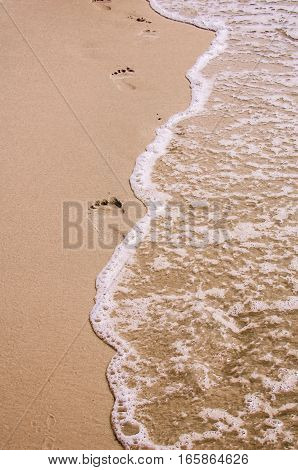 Footprints in the sand.  Ocean beach scene with waves in steps imprinted into wet tropical sands.  Scenic travel destination location with concept of relaxation and leisure.