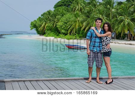 Young couple on the honeymoon vacation on the beach near the sea,  a woman hugs her husband, happiness, and positive emotions in the summer. Boat and palms on the background