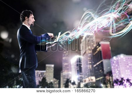 Businessman working with laptop with light effects on the city background. Work with new connections concept