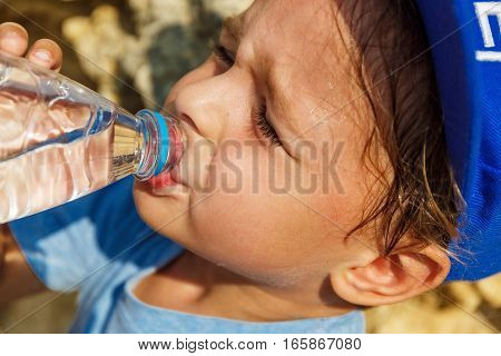 Little boy is drinking water on a hot sunny day