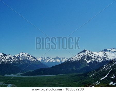 Amazing view of towering peaks while hiking in Alaska. Beautiful landscape on a calm spring or summer day.