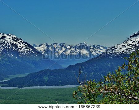 Amazing view of towering mountain peaks. Sunny spring or summer day while hiking in Alaska.