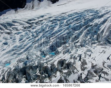 Vivid blue color of Alaska glacier for background. Awesome pattern or texture of glacier ice on mountainside.