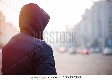Hipster man in hood walking on city street in the evening