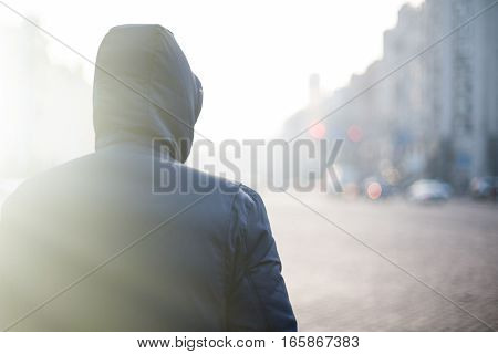 Lonely hipster man in hood walking on city street