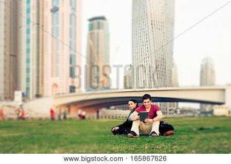 a tourist couple is taking a break, sitting in the grass near dubai marina.
