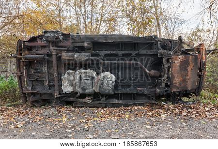 Rusty burned out SUV on it side. On the background of trees and fallen leaves