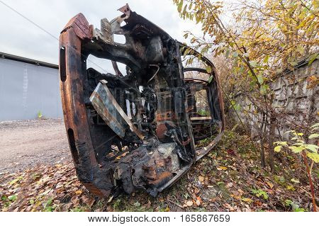 Rusty burned-out SUV on its side. Near the concrete fence on the background of trees and fallen leaves