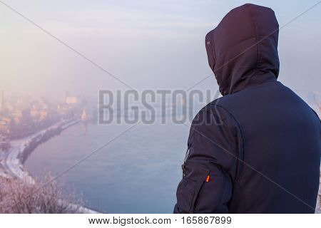 Hipster man traveler in hood looking at winter city landscape