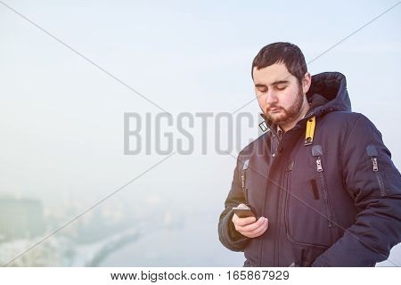 Man traveler using cellphone against winter cityscape