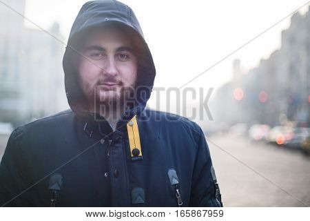 Man traveler with beard in hood looking at camera