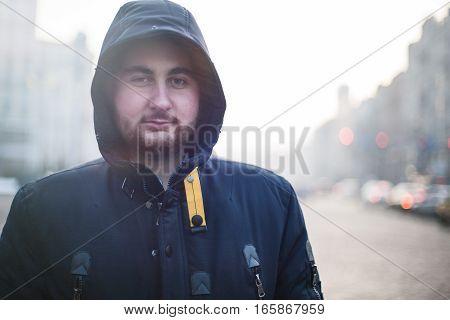 Man traveler with beard in hood looking at camera