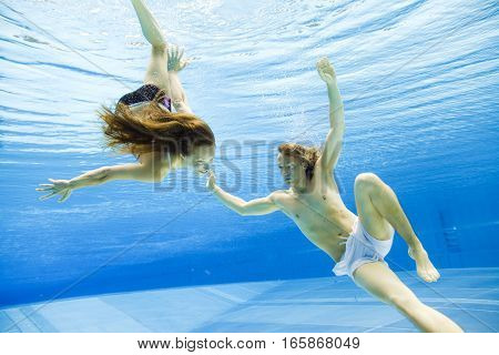 a young couple is swimming in a pool