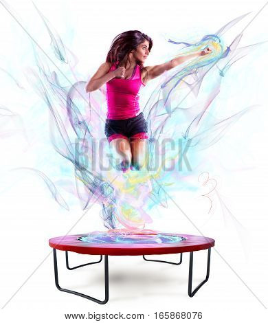 Fitness teacher jumps nimbly on the trampoline with colour light effect
