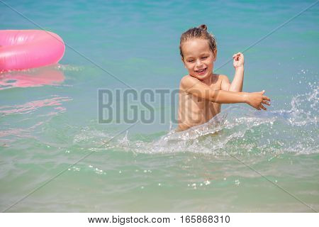 Happy little boy is playing in the sea