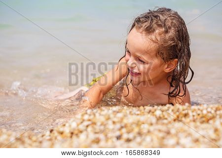 Tanned long-haired boy on the rocky shore