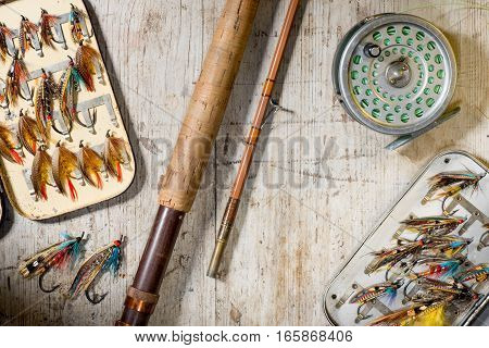Fly fishing rod reel and vintage salmon flies in boxes on a distressed white wooden background