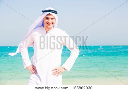 young arabian man standing on the beach