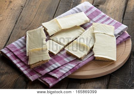 slices of cheese on bread toasts on a wooden background