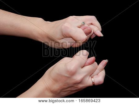 The double fig sign or the combination of three fingers is an obscene gesture commonly used to deny a request. Hands isolated on black background