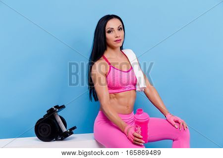 Muscular woman in pink leggings, top and gloves having a rest, sitting and holding shaker, bottle