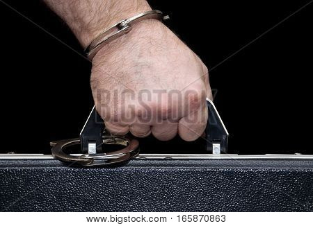 Man's hand handcuffed to a briefcase isolated on black background
