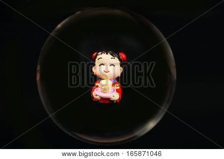 Chinese doll through glass spear cny on black background