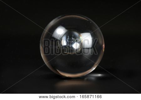 Glass marble refraction through glass crystal ball on black background