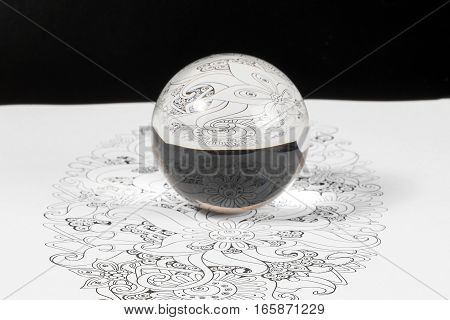 Glass Crystal Ball Reflection over design art refraction on black background