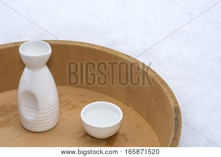 Tokkuri(sake bottle) and Choko(small sake cup) on wood tub with snow