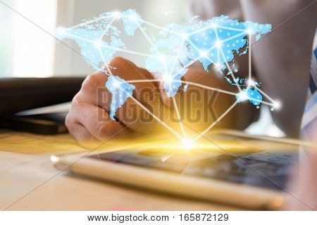 Businessman using computer tablet and finger touching screen with orange light and show blue world map with network conncection line technology conceptual internet globalization concept