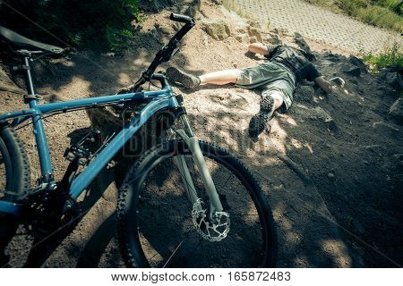 Young mountain biker fallen off his bike when going down a dangerous trail