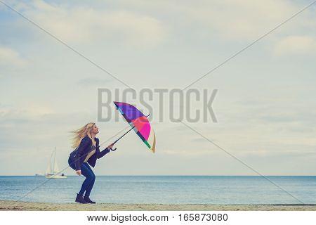 Happiness enjoying cold autumn weather feeling great concept. Woman jumping with colorful umbrella on beach near sea sunny day and clear blue sky