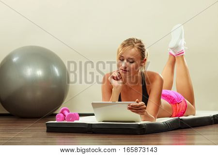 Fitness woman blonde fit girl lying on floor and looking into tablet pc