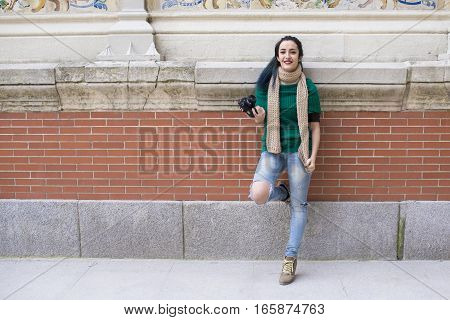 Young woman with camera In front of the Palacio de Cristal in Madrid