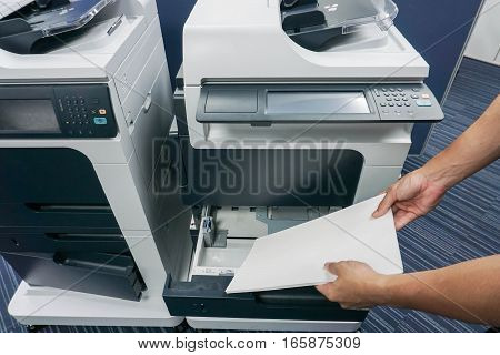businessman put paper sheet into printer tray