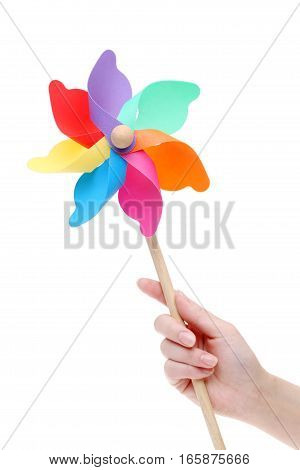 Hand holding colorful toy pinwheel on white background