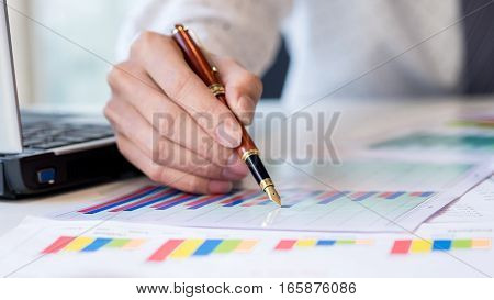 Working process startup. Businessman working at the wood table with new finance project. Modern notebook on table. Pen holding hand