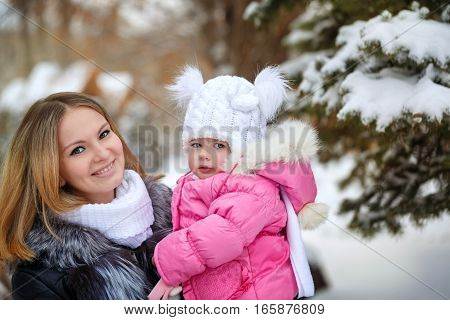 Mother holds daughter on hands outdoors. Related arms. Family walk in a winter park. Family happiness.