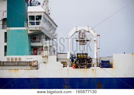 A shot of a ship showing the pattern of blue and white of super structure and hull and equipment on deck.