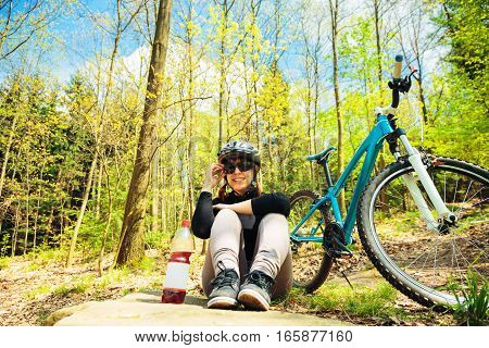 Young woman riding her mountain bike through the summer forest.